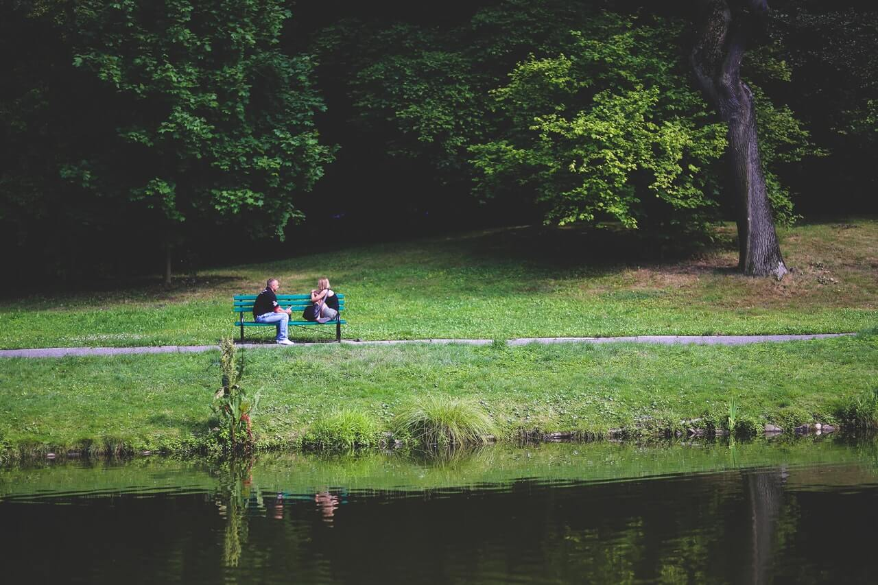 couple sitting on a bench by the river bank
